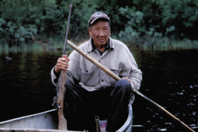 Frank Duck sits in canoe with a paddle and gun in hand.